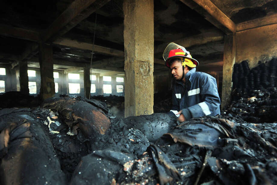 A Bangladeshi police official inspects the burnt garment factory in the Savar neighborhood outside Dhaka, Bangladesh, Sunday Nov. 25, 2012. At least 112 people were killed in a late Saturday night fire that raced through the multi-story garment factory just outside of Bangladesh's capital, an official said Sunday.(AP Photo/ khurshed Rinku) / AP