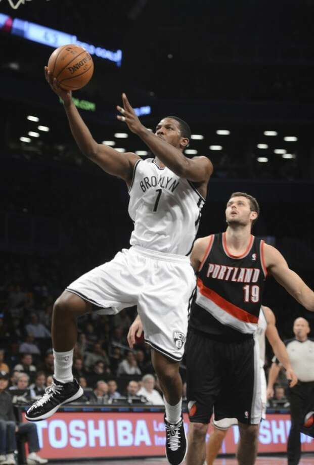 Brooklyn Nets' Joe Johnson, left, drives by Portland Trail Blazers' Joel Freeland in the first quarter of an NBA basketball game at the Barclays Center, Sunday, Nov. 25, 2012, in New York. (AP Photo/Henny Ray Abrams)