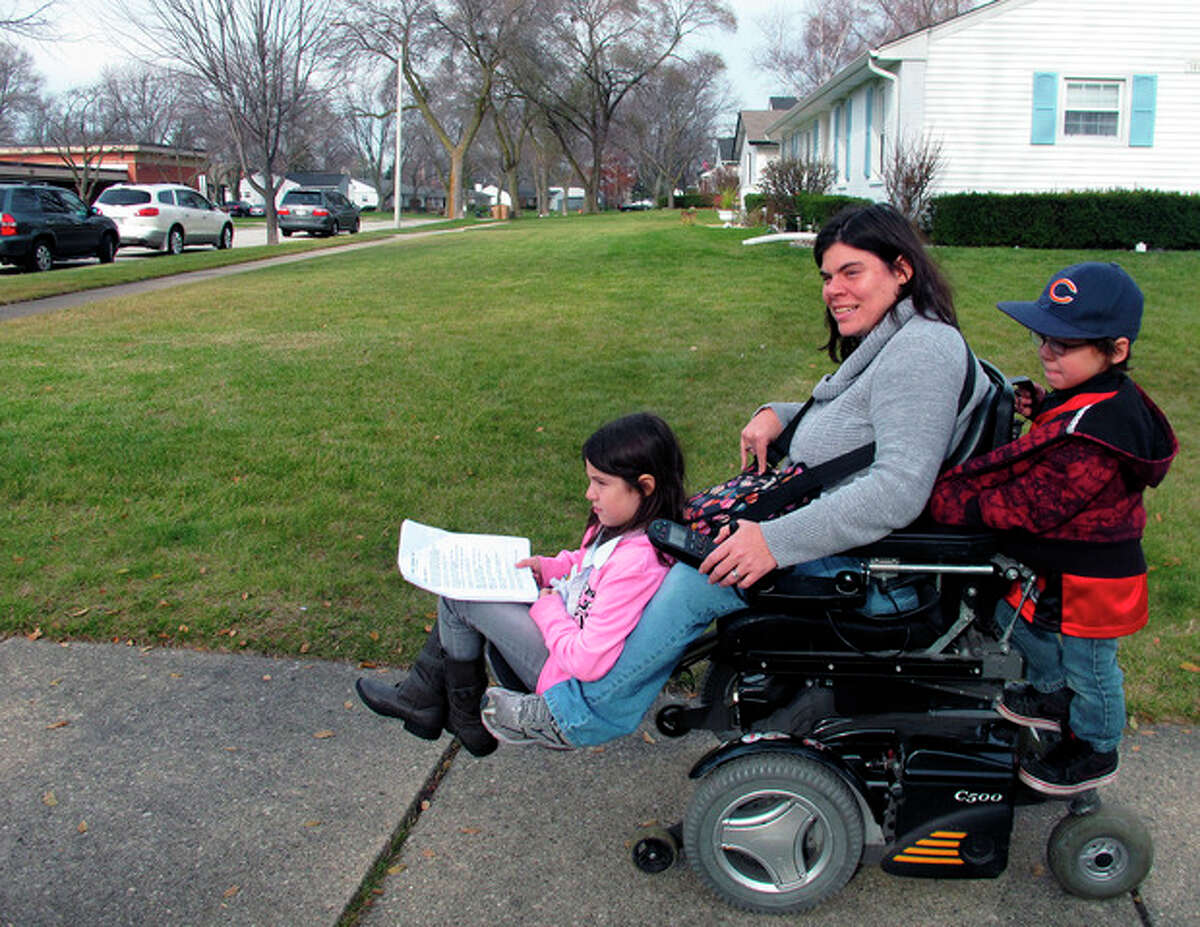 """In this Nov. 19, 2012 photo, twins Abigail and Noah Thomas, 8, ride on the motorized wheelchair of their mother, Jenn Thomas, on their way to a school book fair in Arlington Heights, Ill. Thomas, a 36-year-old mom who has cerebral palsy, says her twins occasionally complain about having to do a few extra chores around the house to help her. Abigail nods and smiles upon hearing this, but says for the most part, their lives are """"kind of normal."""" For her, having a mom with a disability is just how it is, she said. (AP Photo/Martha Irvine)"""