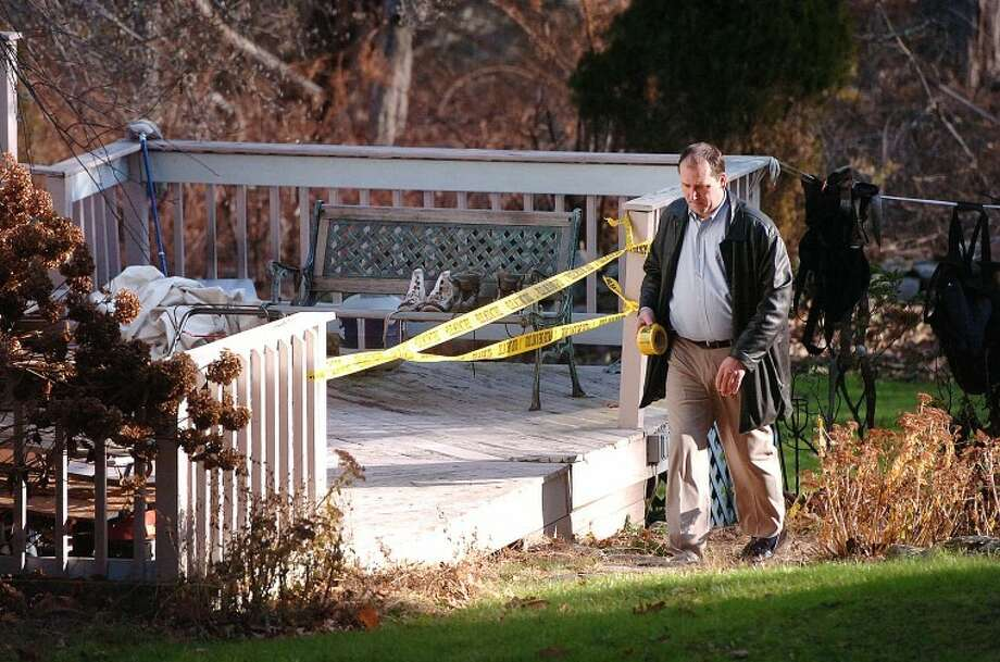 Hour Photo Alex von Kleydorff; Wilton Police Detective Scott Sear wraps police tape over the entrance to a deck on the side of a house at 35 Grumman Ave in Wilton on Monday morning