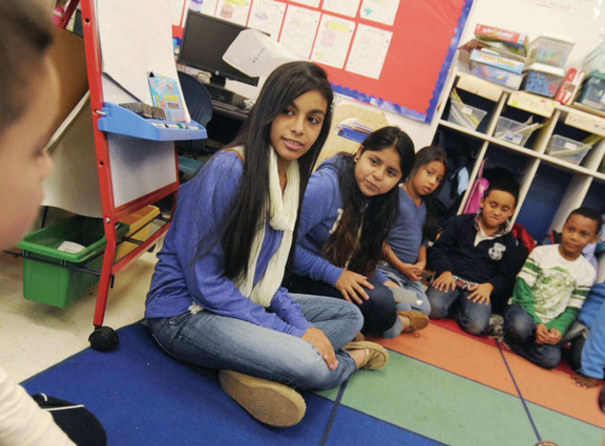 Hour photo/Matthew Vinci Brien McMahon students Alayne Martinez and Mirella Fernandez speak to Brookside Elementary second- graders Monday about Thanksgiving and sharing.