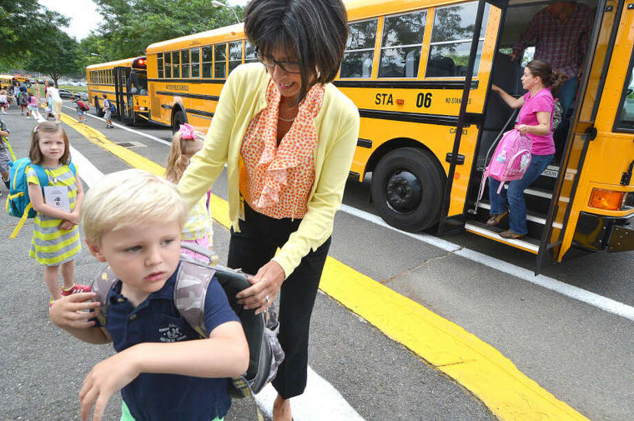 Hour Photo/Alex von Kleydorff . Teacher Maureen Clancy helps Oliver Adams get his backpack on as he heads to his first day of Kindergarten at Miller Driscoll school in Wilton