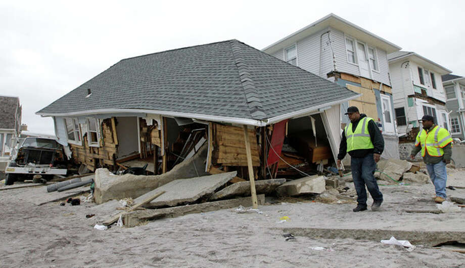 FILE - In this Monday, Nov. 19, 2012 file photo, utility workers walk past a badly damaged house in the Belle Harbor neighborhood of the Rockaways, in New York. The house is one of 200 homes that has been designated unsafe by the New York City Department of Buildings because of damage from Superstorm Sandy. Sandy ran up a $42 billion bill on New York and the state and New York City are making big requests for disaster aid from the federal government, according to one of Gov. Andrew Cuomo's administration officials. (AP Photo/Kathy Willens, File) / AP