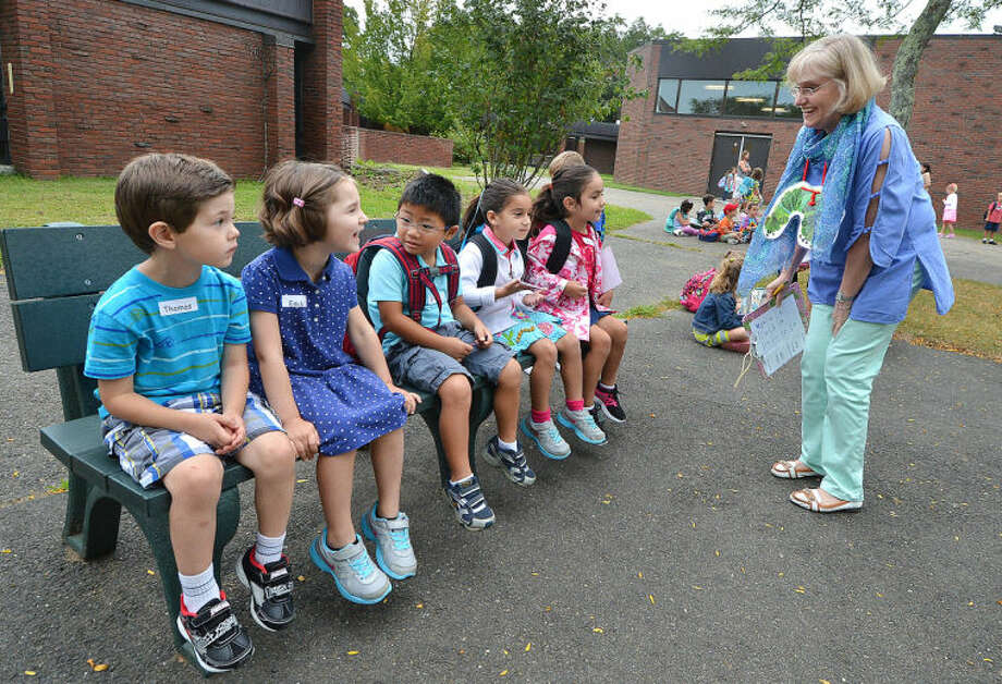 Hour Photo/Alex von Kleydorff . Teacher Carol Maxwell has her kids attention as they gather in front of the school for first day at Miller Driscoll in Wilton.