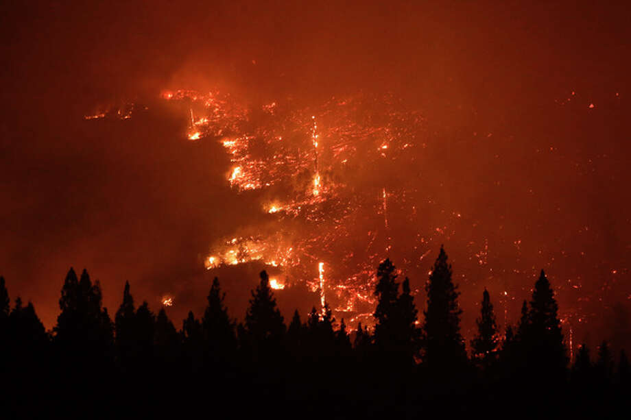 A forest smolders as the Rim Fire continues to burn near Yosemite National Park, Calif., on Saturday, Aug. 24, 2013. Fire crews are clearing brush and setting sprinklers to protect two groves of giant sequoias as a massive week-old wildfire rages along the remote northwest edge of Yosemite National Park. (AP Photo/Jae C. Hong) / AP