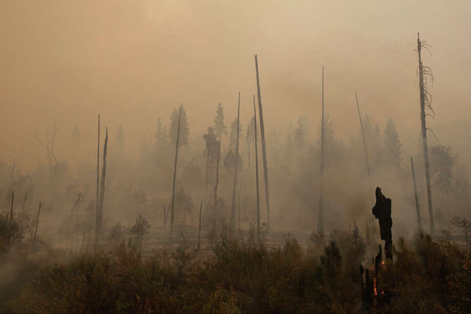 A smoke rises from smoldering trees as firefighters continue to battle the Rim Fire near Yosemite National Park, Calif., on Sunday, Aug. 25, 2013. With winds gusting to 50 mph on Sierra mountain ridges and flames jumping from treetop to treetop, hundreds of firefighters have been deployed to protect this and other communities in the path of the Rim Fire raging north of Yosemite National Park. (AP Photo/Jae C. Hong) / AP