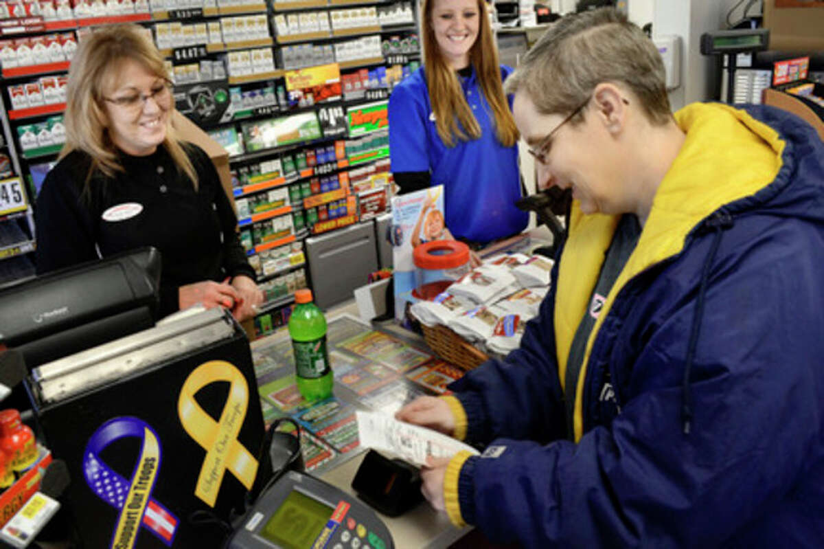 Manager Julie Rebennack, left, and customer service representative Megan Horn wish Lori Soule, 48, right, good luck after Soule purchased a Powerball ticket Monday, Nov. 26, 2012, at a Speedway convenience store in Marion, Ind. Wednesday's Powerball jackpot will be a predicted $425 million, the game's largest jackpot ever. (AP Photo/The Chronicle-Tribune, Jeff Morehead)