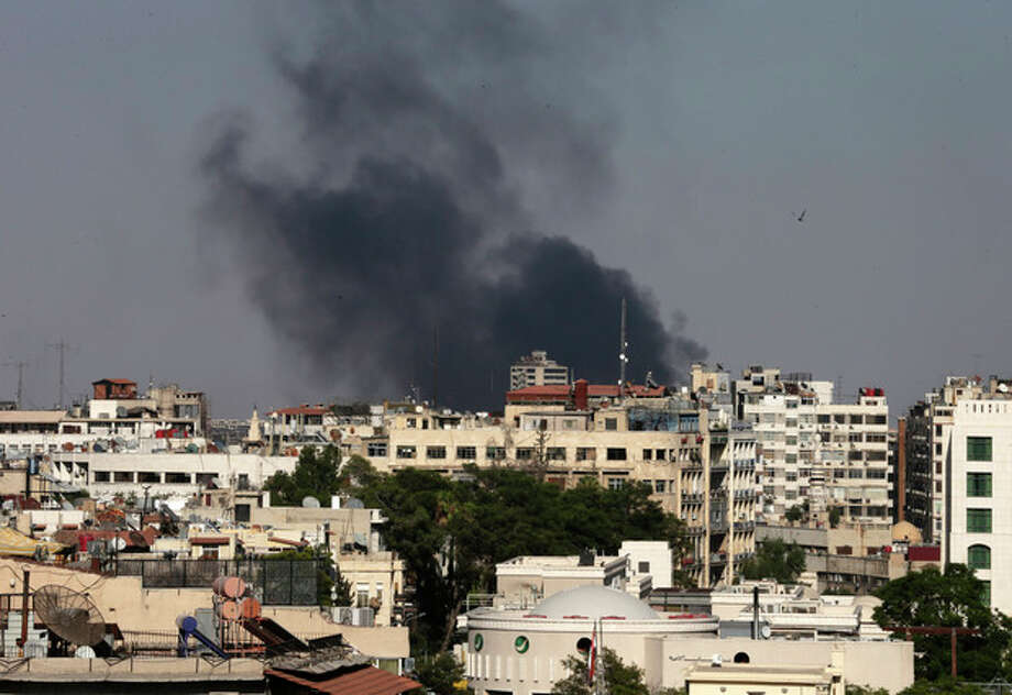 Black columns of smoke rise from heavy shelling in the Jobar neighborhood, east of Damascus, Syria, Sunday, Aug. 25, 2013. Syria reached an agreement with the United Nations on Sunday to allow a U.N. team of experts to visit the site of alleged chemical weapons attacks last week outside Damascus, state media said. (AP Photo/Hassan Ammar) / AP