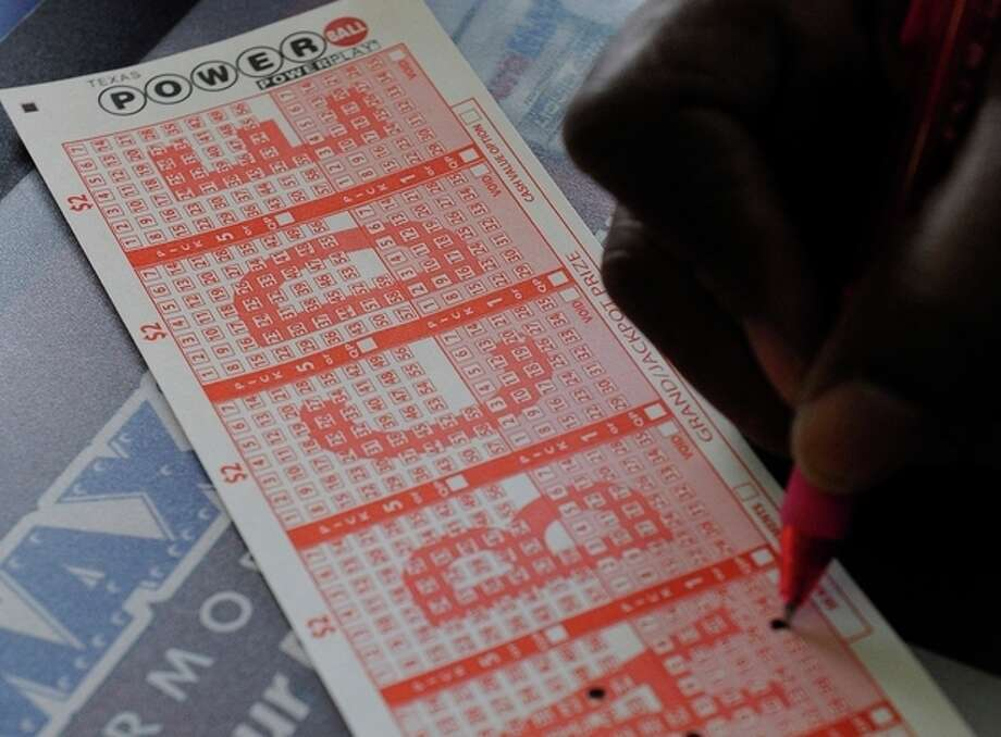 A customer fills in his numbers on a Powerball ticket for a chance to win the $450,000 jackpot Monday, Nov. 26, 2012, in Houston for a chance to win the $450,000 jackpot. (AP Photo/Pat Sullivan) / AP