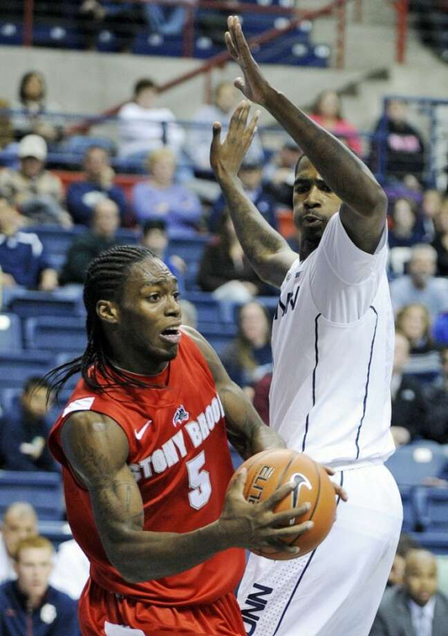 Stony Brook's Dave Coley, left, looks to pass while guarded by Connecticut's Phillip Nolan during the first half of an NCAA college basketball game in Storrs, Conn., Sunday, Nov. 25, 2012. (AP Photo/Fred Beckham)