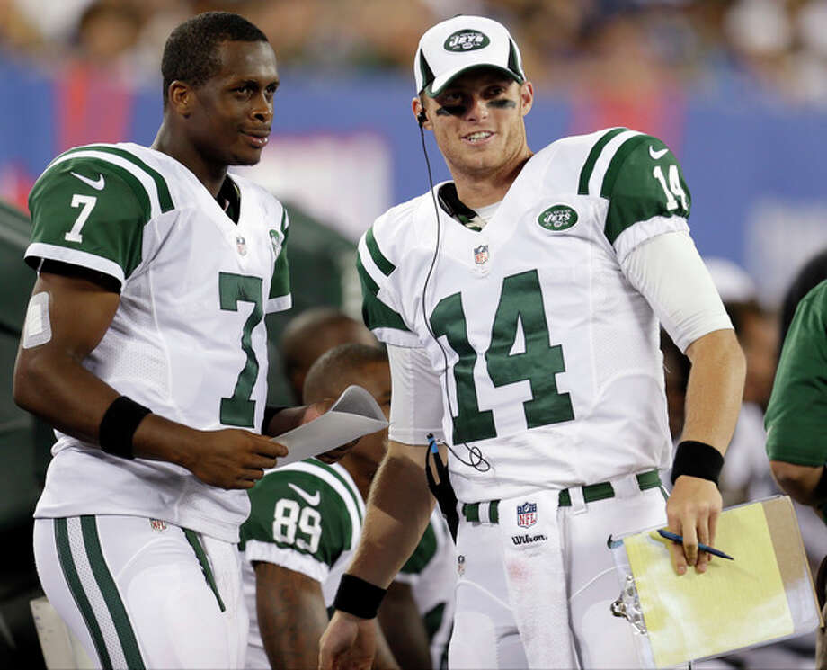 New York Jets quarterbacks Geno Smith (7) and Greg McElroy (14) talk during the first half of a preseason NFL football game against the New York Giants, Saturday, Aug. 24, 2013, in East Rutherford, N.J. (AP Photo/Julio Cortez) / AP