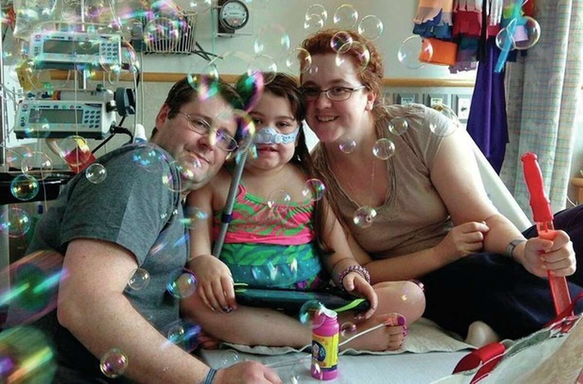AP file photo / Murnaghan Family In this May 30 file photo provided by the Murnaghan family, Sarah Murnaghan, center, celebrates the 100th day of her stay in Children's Hospital of Philadelphia with her father, Fran, left, and mother, Janet. The 10-year-old suburban Philadelphia girl received lung transplants there June 12, which failed, and again three days later, her family said.