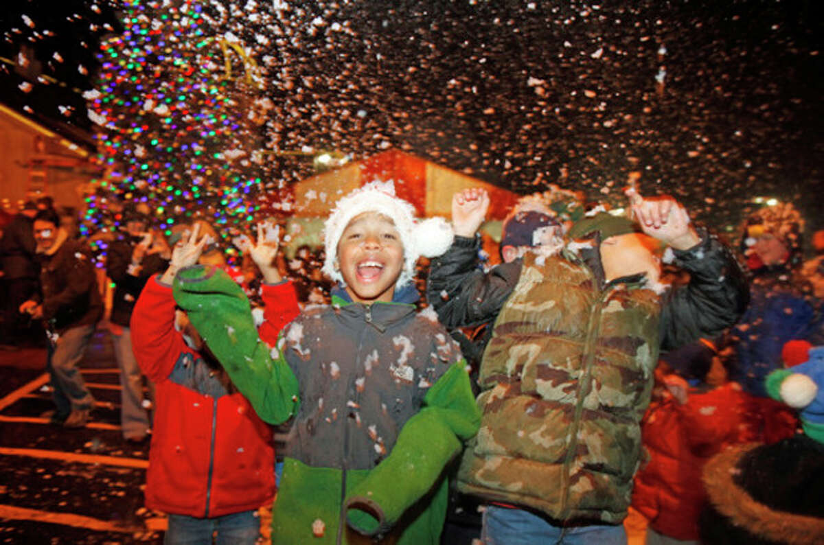 Jayden King, 10, plays in the snow with his friends during Stew Leonard's annual tree lighting Tuesday evening. Hour Photo / Danielle Robinson