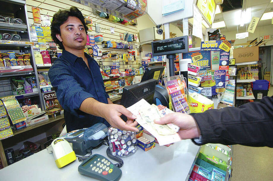 Hour photo / Alex von KleydorffSai Charan passes some purchased Powerball tickets to a customer at Jet Variety in Broad River on Tuesday. / 2012 The Hour Newspapers