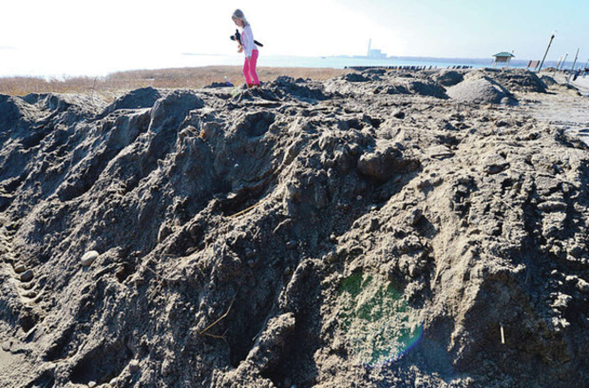 6 year old Julia Perry played on the piles of sand Friday that were cleared from areas of Calf Pasture Beach. CThe beach reopened despite lasting destruction from Hurricane Sandy. Hour photo / Erik Trautmann