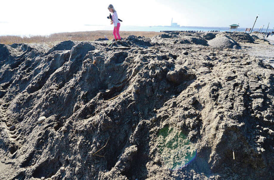 6 year old Julia Perry played on the piles of sand Friday that were cleared from areas of Calf Pasture Beach. CThe beach reopened despite lasting destruction from Hurricane Sandy.Hour photo / Erik Trautmann / (C)2012, The Hour Newspapers, all rights reserved