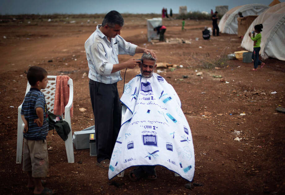 FILE - In this Thursday, Nov. 8, 2012 file photo, a Syrian man who fled from the violence in his village, sits for a haircut next to his tent at a camp, in the Syrian village of Atmeh, near the Turkish border with Syria. A dark realization is spreading across north Syria that despite 20 months of violence and recent rebel gains, an end to the war to topple President Bashar Assad is nowhere in sight. (AP Photo/Khalil Hamra, File) / AP