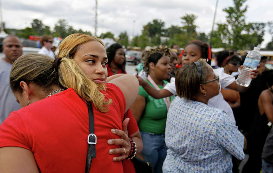 Shanique Worthey, right, is embraced by her mother Daphne Morris, while waiting to be reunited with her son five-year-old son Skyler Worthey as students from Ronald E. McNair Discovery Learning Academy are picked up by loved ones in a Walmart parking lot after they were evacuated when a gunman entered the school, Tuesday, Aug. 20, 2013, in Decatur, Ga. (AP Photo/David Goldman) / AP