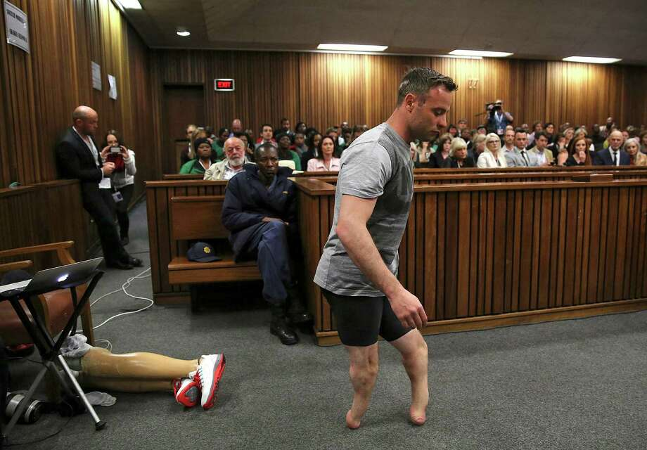 Oscar Pistorius, the South African Olympian, removes his prosthetic legs and walks across the courtroom during his sentencing trial on Wednesday. Photo: SIPHIWE SIBEKO, POOL / POOL