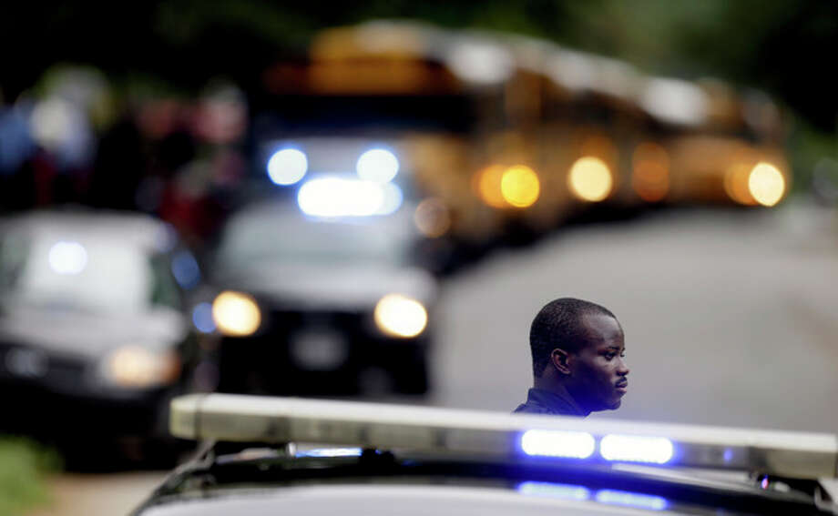 A Dekalb County Police officer stands guard as students from Ronald E. McNair Discovery Learning Academy board school buses to take them to reunite with their parents after they were evacuated after reports of a gunman entered the school, Tuesday, Aug. 20, 2013, in Decatur, Ga. All students and teachers are safe and a suspect is in custody after gunfire was heard at the Atlanta-area elementary school today. (AP Photo/David Goldman) / AP