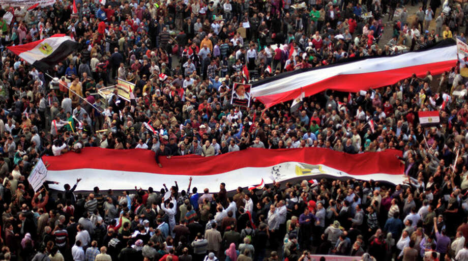 Egyptian protesters carry large national flags in Tahrir Square in Cairo, Egypt, Tuesday, Nov. 27, 2012. Thousands flocked to Cairo's central Tahrir square on Tuesday for a protest against Egypt's president in a significant test of whether the opposition can rally the street behind it in a confrontation aimed at forcing the Islamist leader to rescind decrees that granted him near absolute powers. (AP Photo/ Khalil Hamra) / AP