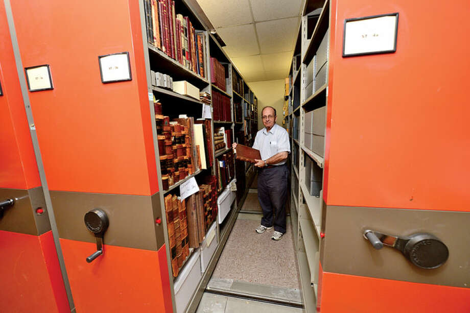 Town historian and library volunteer Ralph Bloom looks over records of 19th century manufacturing in Norwalk in the library's new History Room. Hour photo / Erik Trautmann