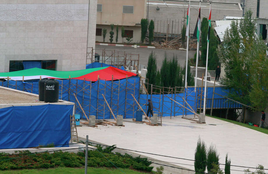 Blue tarp covers the entrance to Yasser Arafat's mausoleum in the West Bank city of Ramallah. The remains of the late Palestinian leader Yasser Arafat were exhumed from his grave on Tuesday so international forensic experts could search for additional clues to his death, Palestinian officials said. (AP Photo/Nasser Shiyoukhi) / AP
