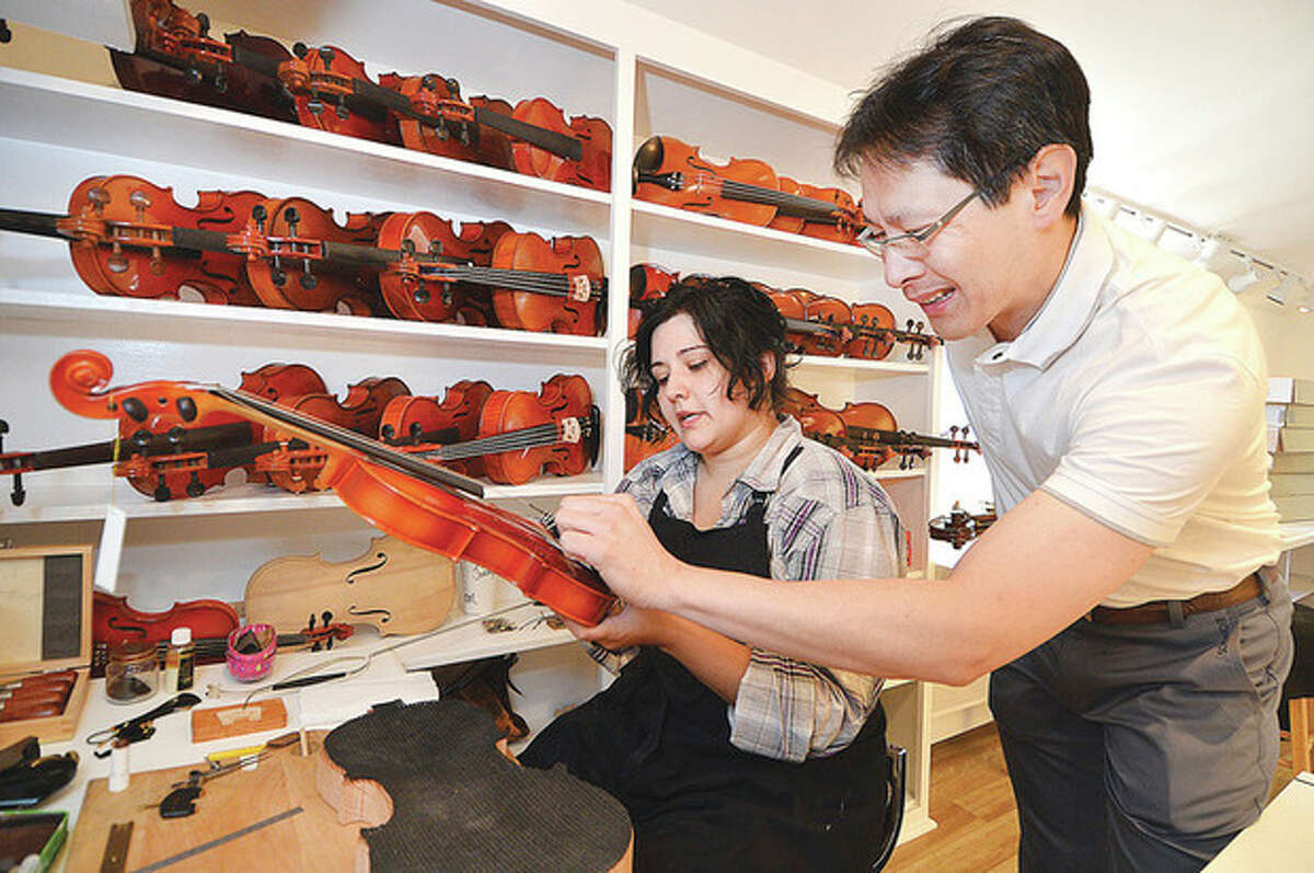 Hour Photo/Alex von Kleydorff Kenneth Kuo, president and CEO of RentalInstrument.com, works on a new shipment of violins with luthier Jennifer Martins.