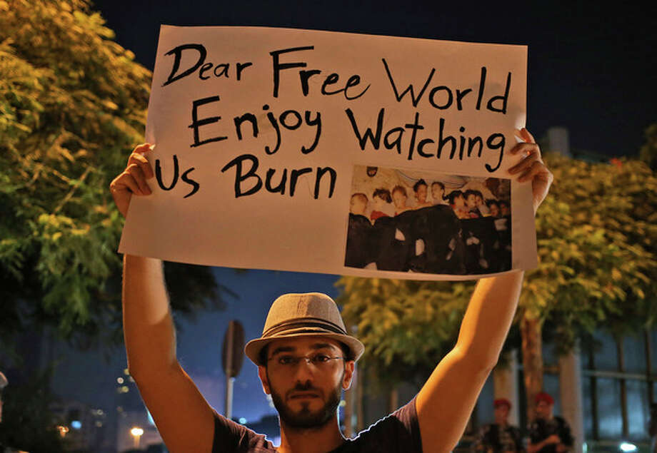 A Syrian man who lives in Beirut, holds up a placard during a vigil against the alleged chemical weapons attack on the suburbs of Damascus, in front the United Nations headquarters in Beirut, Lebanon, Wednesday, Aug. 21, 2013. Anti-government activists accused the Syrian regime of carrying out a toxic gas attack that is thought to have killed at least 100 people, including many children as they slept, during intense artillery and rocket barrages Wednesday on the eastern suburbs of Damascus that are part of a fierce government offensive in the area. (AP Photo/Hussein Malla) / AP