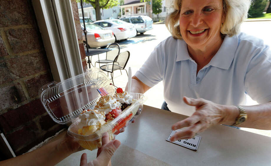"Sally Bane is handed the banana split sundae she ordered ""to go"" from the window at the Valley Dairy in Latrobe, Pa., Wednesday Aug. 21, 2013. A weekend of festivities are planned to surround the dedication of a Pennsylvania Historical and Museum Commission marker to be dedicated Friday, Aug. 23 that acknowledges apprentice pharmacist David E. Strickler for inventing the banana split there in 1904. (AP Photo/Keith Srakocic) / AP"
