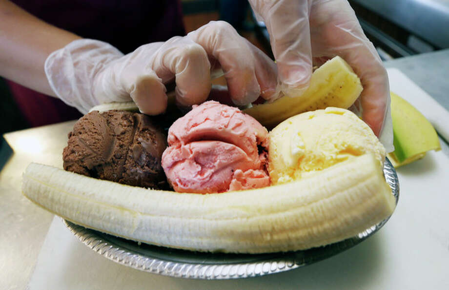 Kylie Polinsky places the other half of a split banana behind the three scoops of ice cream as she prepares a banana split sundae Wednesday Aug. 21, 2013, at the Valley Dairy in Latrobe, Pa. A weekend of festivities are planned to surround the dedication of a Pennsylvania Historical and Museum Commission marker to be dedicated Friday, Aug. 23 that acknowledges apprentice pharmacist David E. Strickler for inventing the banana split there in 1904. (AP Photo/Keith Srakocic) / AP