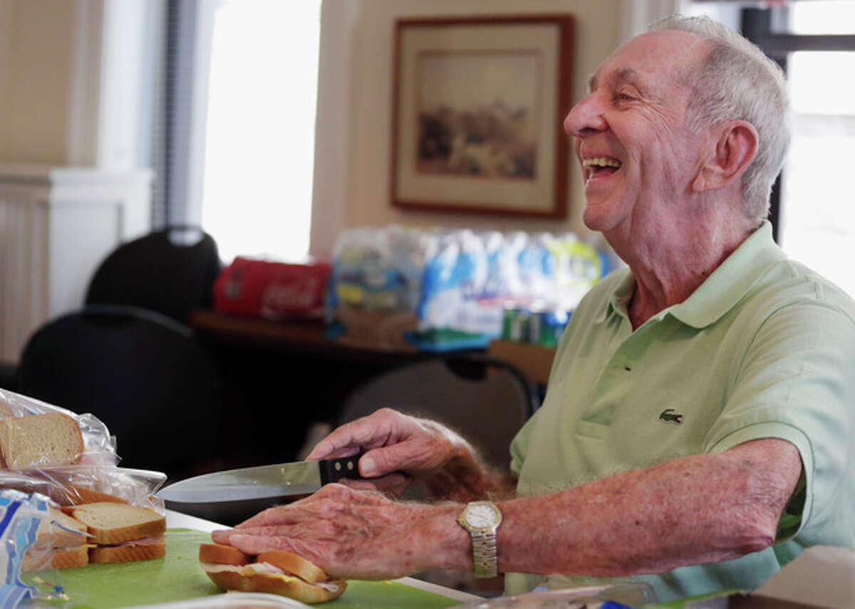 """In this Aug. 1, 2013 photo, 85-year-old Don Tenbrunsel a soup kitchen volunteer, laughs with other volunteers as he works making lunches at St. Josaphat?'s Church in Chicago. Tenbrunsel is a ?""""super ager,?"""" participating in a Northwestern University study of people in their 80s and 90s with astounding memories. So far the research has found scientific evidence that brains in this elite group resemble those of people decades younger. (AP Photo/M. Spencer Green)"""