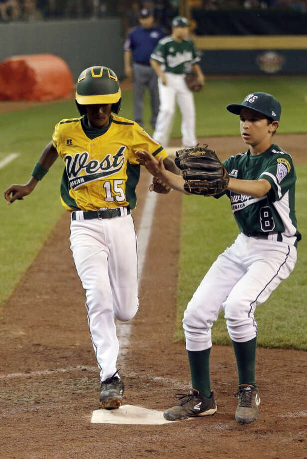 Chula VIsta, Calif.'s Michael Gaines (15) scores on a wild pitch by Westport, Conn., pitcher Alex Reiner, right, in the sixth inning of a baseball game at the Little League World Series in South Williamsport, Pa., Wednesday, Aug. 21, 2013. Chula Vista won 6-3. (AP Photo/Gene J. Puskar)