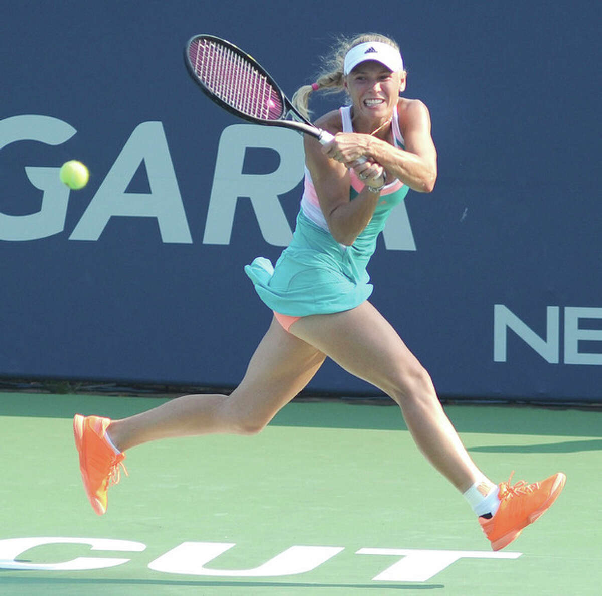 Hour photo/John Nash Caroline Wozniacki hits a return while on the run during her second round match against Karin Knapp Wednesday at the New Haven Open at Yale. Wozniacki won, 6-1, 7-5.