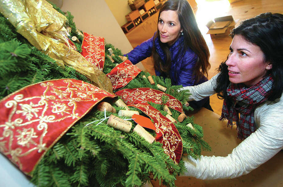 Hour Photo/Alex von Kleydorff. L-R Event Co-Chairs Torie Clancey and Sonia O'Connor place a handmade wreath up on the wall of the Carriage barn at Ambler Farm. This Friday night kicks off Ambler farm's Annual Greens sale and the wreaths are part of an evening of food, drink and silent auction of all the hand made wreaths. Go to amblerfarm.org for more info. / 2012 The Hour Newspapers/Alex von Kleydorff