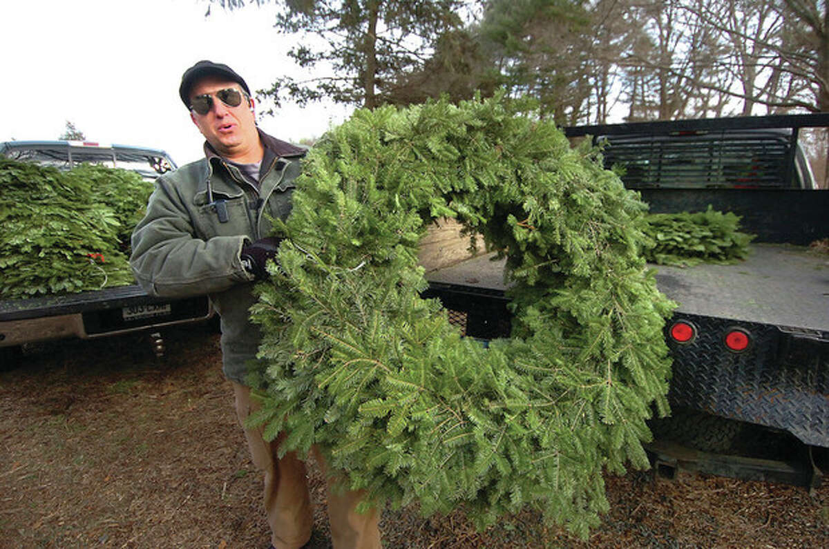 Hour Photo/Alex von Kleydorff Manager Lou Bacchiocchi unloads some of the 36-inch wreaths at the CT Audubon Society Christmas tree farm in Westport.