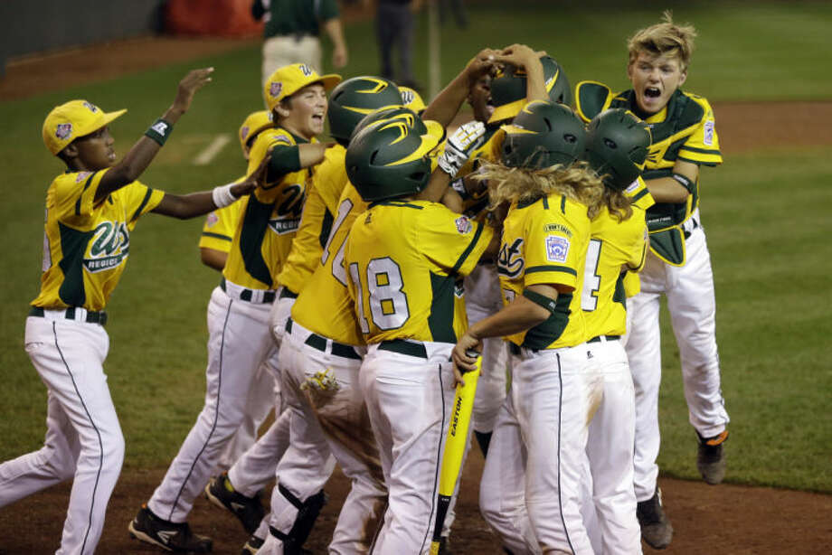 Chula VIsta, Calif.'s Grant Holman is swarmed by celebrating teammates after hitting a three-run home run off Westport, Conn., pitcher Max Popken in the ninth inning of a baseball game at the Little League World Series tournament in South Williamsport, Pa., Wednesday, Aug. 21, 2013. The team from Chula Vista, Calif., won 6-3. (AP Photo/Gene J. Puskar)