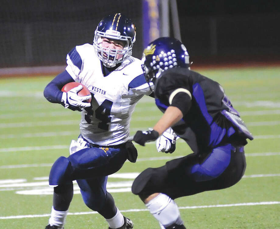 Hour photo/John NashWeston running back Peter Lummis, left, tries to get around an Ellington/Somers defender during Wednesday night's state playoff game. Sidelined by an injury earlier in the season, Lummis has returned to become a big part of the Trojans' game plan.