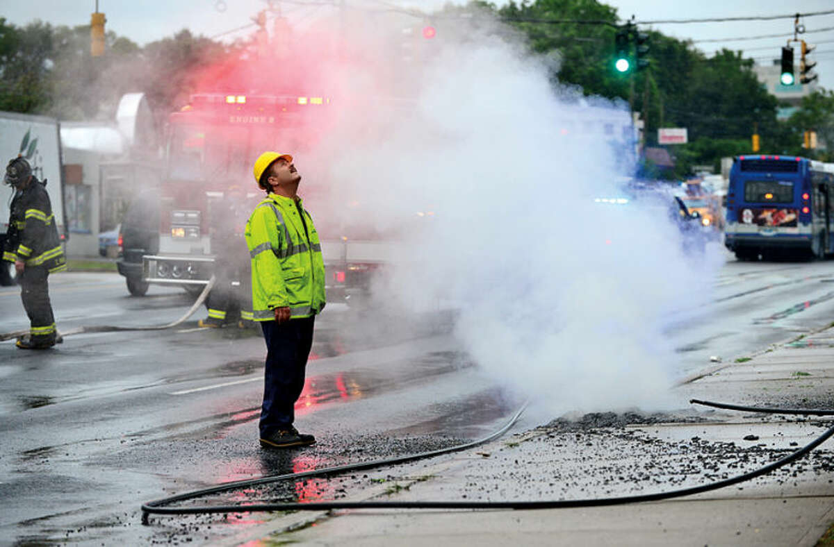 CL&P workers examine the damage left by lightening strikes that brought down wires on Connecticut Ave. Thursday morning. Hour photo / Erik Trautmann