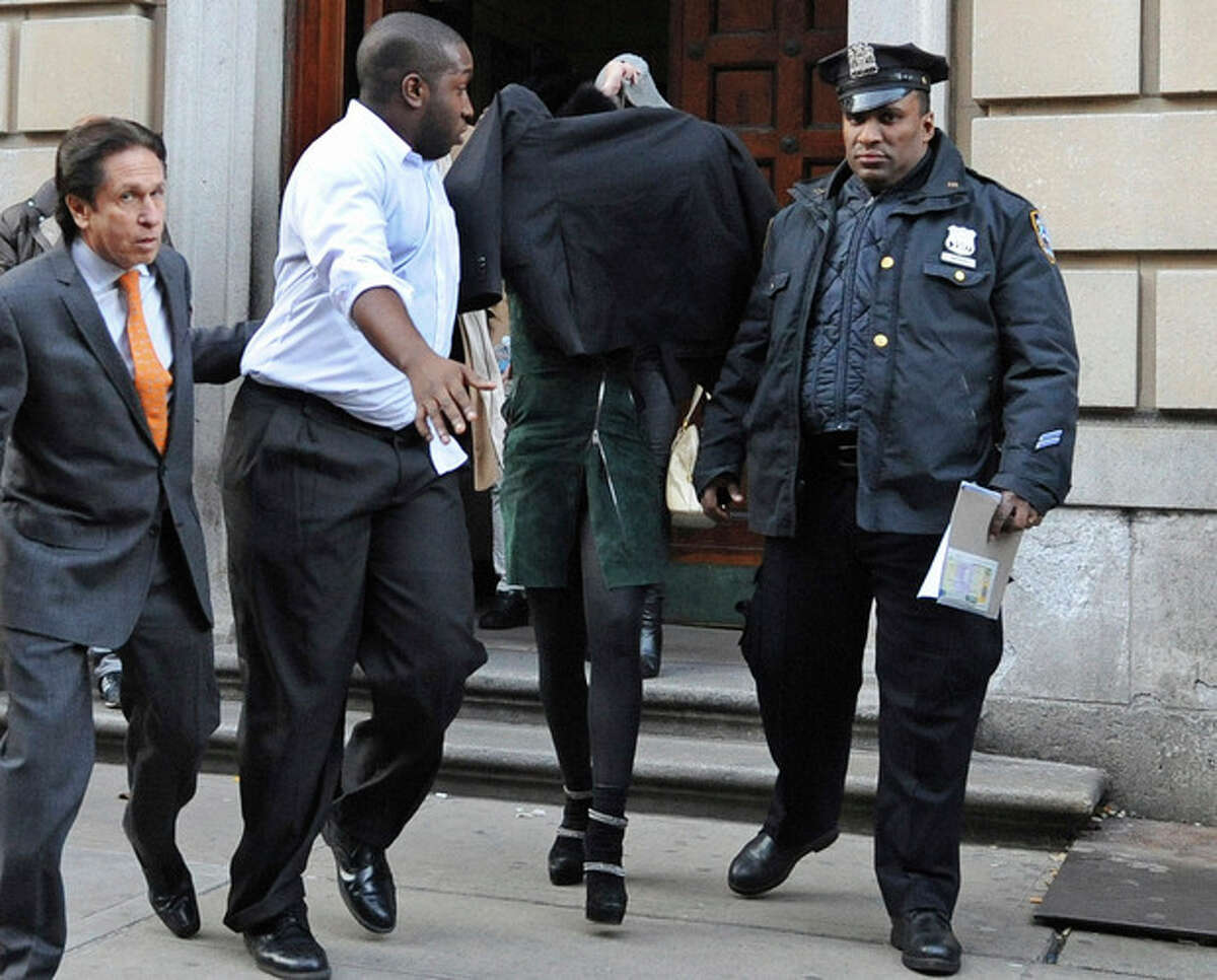 AP Photo/ Louis Lanzano Lindsay Lohan, second from right, is escorted from the 10th Precinct police station, with her face shielded, Thursday, Nov. 29, in New York after being charged for allegedly striking a woman at a nightclub.