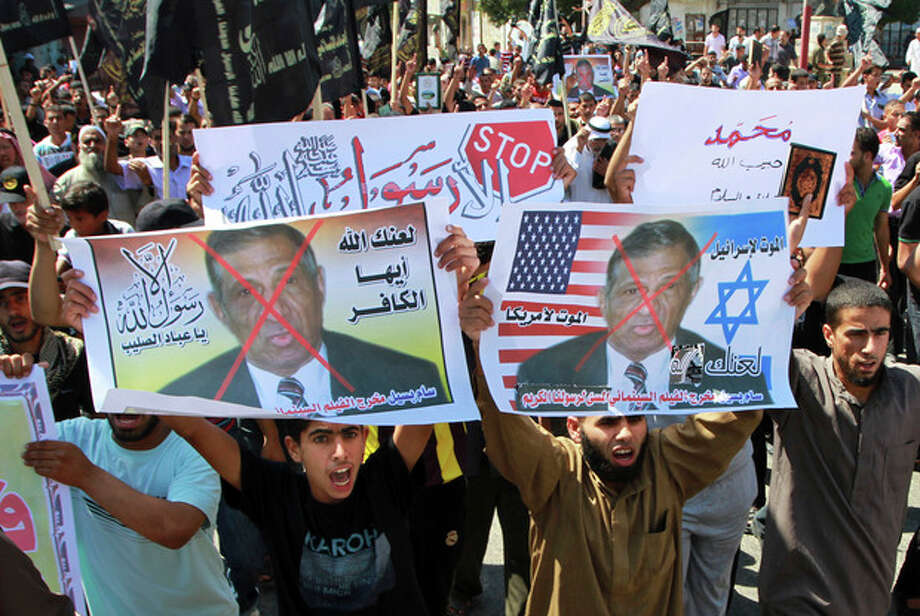 """FILE - In this Friday, Sept. 14, 2012 file photo, Palestinian Islamic Jihad supporters rally with banners depicting Morris Sadek during a protest in Khan Younis, southern Gaza Strip, as part of widespread anger across the Muslim world about a film ridiculing Islam's Prophet Muhammad. The banners in Arabic read, """"Death to Israel,"""" """"death to America"""" and, """"anyone but God's Prophet."""" An Egyptian court on Wednesday, Nov. 28, 2012 has convicted in absentia seven Egyptian Coptic Christians and a Florida-based American pastor and sentenced them to death on charges linked to an anti-Islam film that had sparked riots in parts of the Muslim world. (AP Photo/Adel Hana, File) / AP"""