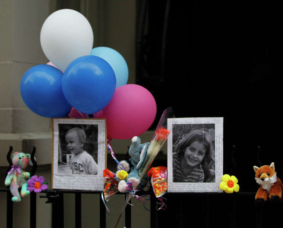 FILE - In this Oct. 27, 2012 file photo, Photographs of the two children allegedly stabbed by their nanny are displayed alongside balloons and stuffed animals at memorial outside the apartment building were they lived in New York. Yoselyn Ortega, the nanny, has pleaded not guilty in the stabbing deaths of the two children. Ortega was arraigned Wednesday, Nov. 28, 2012 at a hospital where she has been treated for self-inflicted stab wounds. Six-year-old Lucia Krim and her 2-year-old brother, Leo, were killed Oct. 25 in their Upper West Side apartment. Their mother found them when she came home with the victims' 3-year-old sister. (AP Photo/Mary Altaffer) / AP