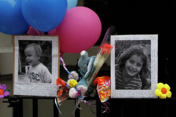 FILE - In this Oct. 27, 2012 file photo, Photographs of the two children allegedly stabbed by their nanny are displayed alongside balloons and stuffed animals at memorial outside the apartment building were they lived in New York. Yoselyn Ortega, the nanny, has pleaded not guilty in the stabbing deaths of the two children. Ortega was arraigned Wednesday, Nov. 28, 2012 at a hospital where she has been treated for self-inflicted stab wounds. Six-year-old Lucia Krim and her 2-year-old brother, Leo, were killed Oct. 25 in their Upper West Side apartment. Their mother found them when she came home with the victims' 3-year-old sister. (AP Photo/Mary Altaffer)
