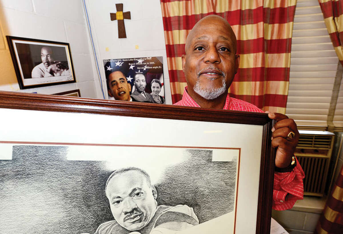 """The Rev. Lindsay Curtis, pastor of Grace Baptist Church in South Norwalk, poses with a portrait of Dr. Martin Luther King, Jr. At 11 years old, Curtis witnessed King's """"I Have a Dream""""speech in Washington, D.C. with his grandparents."""