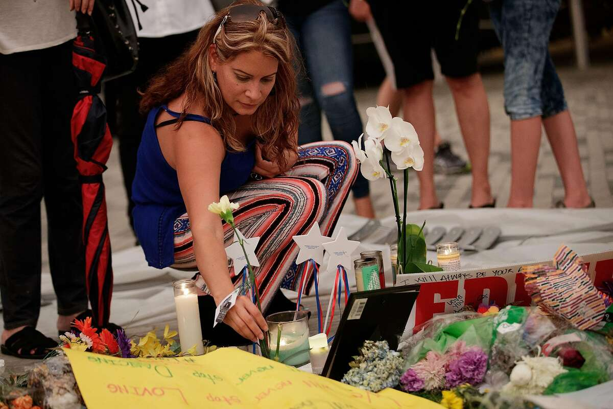 ORLANDO, FL - JUNE 14: A woman leaves flowers at a memorial for the victims of the Pulse Nightclub shooting, at the Dr. Phillips Center for Performing Arts, June 14, 2016 in Orlando, Florida. The shooting at Pulse Nightclub, which killed 49 people and injured 53, is the worst mass-shooting event in American history. (Photo by Drew Angerer/Getty Images)