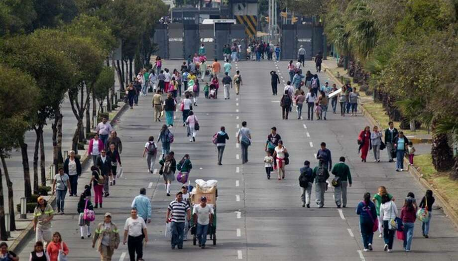 People walk at the barricaded street where Mexico's Congress is located in Mexico City, Monday, Nov. 26, 2012. Police heightened security around the building where Mexico's President-elect Enrique Pena Nieto, of the Institutional Revolutionary Party (PRI) will be sworn-in on Dec. 1. (AP Photo/Eduardo Verdugo) / AP