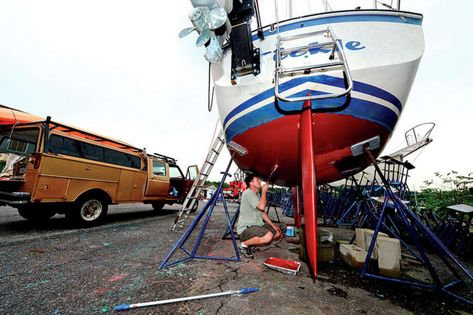 Ken Ellis works on the Tickle at the boat yard at 71 Rowayton Ave. The yard will close and condominiums will be built at 71-76 Rowayton Ave..Hour photo / Erik Trautmann / (C)2013, The Hour Newspapers, all rights reserved