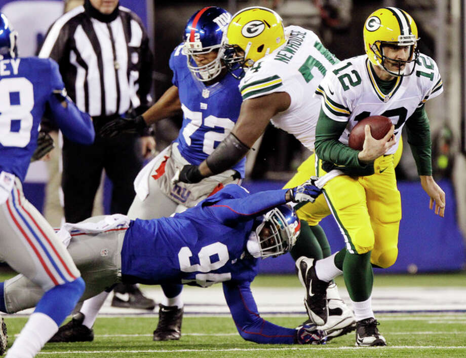 Green Bay Packers quarterback Aaron Rodgers (12) runs away from New York Giants outside linebacker Mathias Kiwanuka (94) during the first half of an NFL football game, Sunday, Nov. 25, 2012, in East Rutherford, N.J. (AP Photo/Kathy Willens) / AP