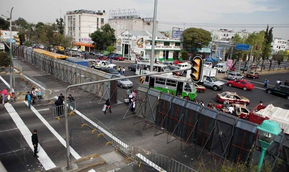 The street where Mexico's Congress is located is shown blocked by a metal barricade in Mexico City, Monday, Nov. 26, 2012. Police heightened security around the building where Mexico's President-elect Enrique Pena Nieto, of the Institutional Revolutionary Party (PRI) will be sworn-in on Dec. 1. (AP Photo/Eduardo Verdugo) / AP