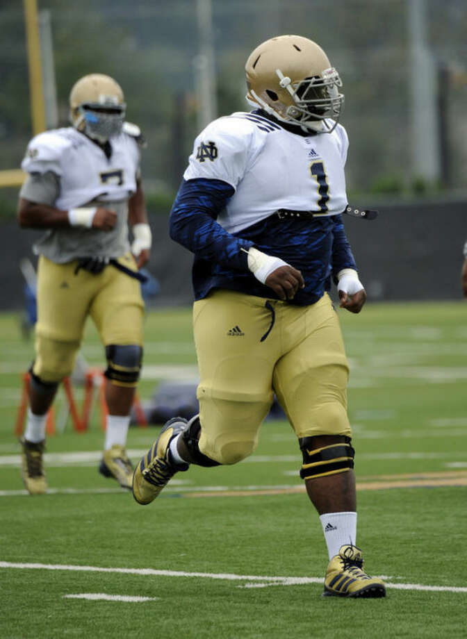 Notre Dame NCAA college football defensive lineman Louis Nix loosens up during practice Thursday Aug. 22, 2013, in South Bend, Ind. (AP Photo/Joe Raymond)
